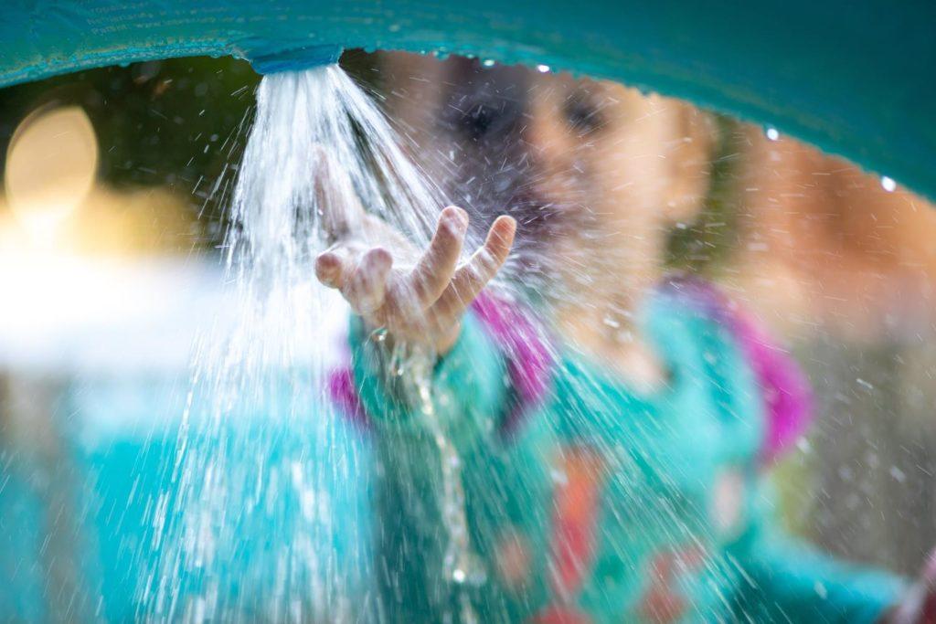Niña disfrutando de sus colonias de verano: pone su mano bajo el chorro de agua en una de las actividades al aire libre.