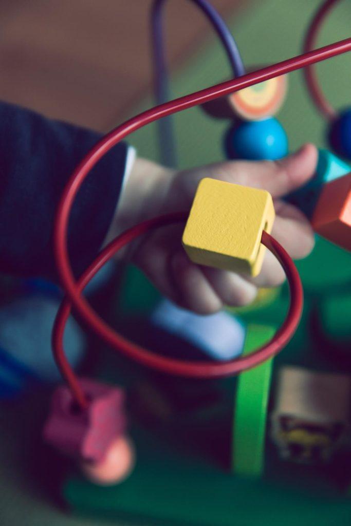 Niño jugando con un cubo de actividades en una terapia ocupacional infantil